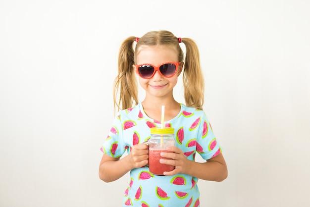 Улыбающаяся девушка, пить свежий арбузный коктейль на белом