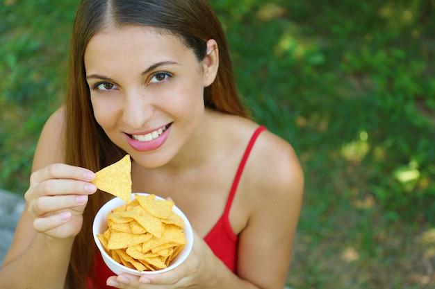 야외 옥수수 칩을 먹고 웃는 소녀. 공간을 복사하십시오.