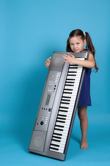 Smiling girl embracing an upright electronic synthesizer