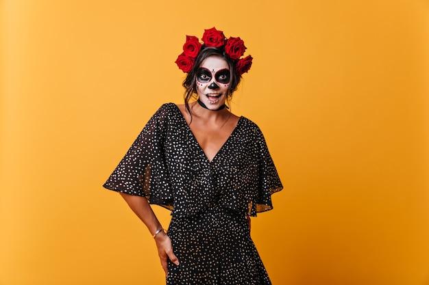 Улыбающаяся девочка эмоционально позирует в мексиканской маске скелета. модель с розами в волосах смеется на оранжевой стене.
