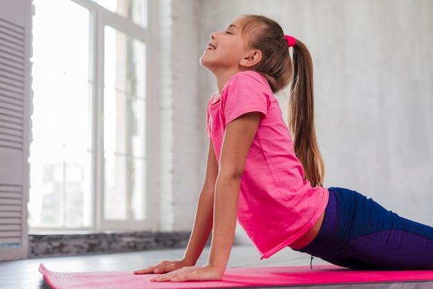 Smiling girl exercising near the window