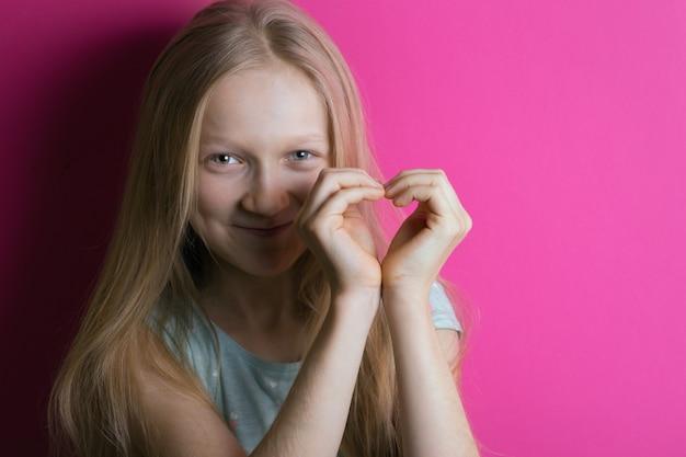笑顔の女の子がハートの形で手を組んだ