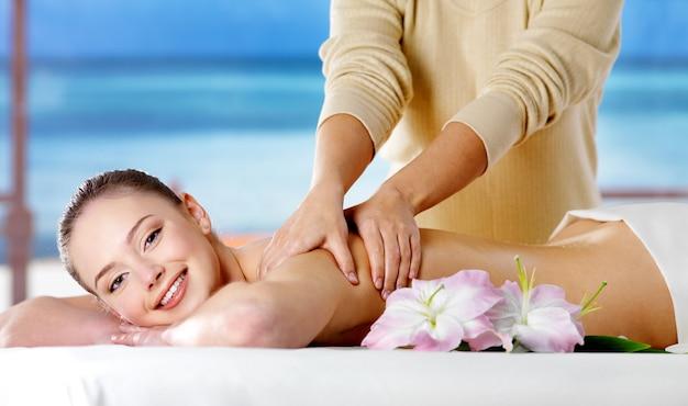 Ragazza sorridente che ottiene massaggio della stazione termale nel salone di bellezza - spazio della natura. al chiuso