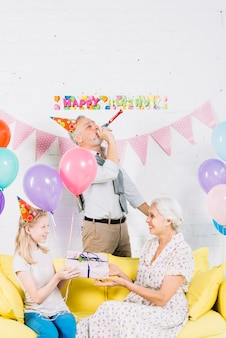 Smiling girl giving gift to her grandmother in front of man blowing party horn