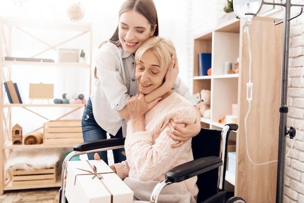 Улыбающаяся девушка дает подарок счастливой старой матери