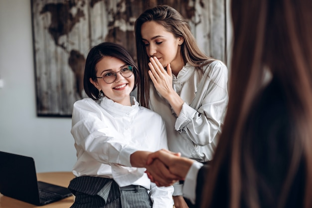 Smiling girl in glasses shakes hands with her colleague while her assistant says something in her ear
