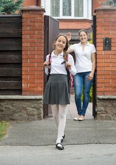 Улыбающаяся девочка выходит из дома в школу. мать стоит в дверях и машет ей