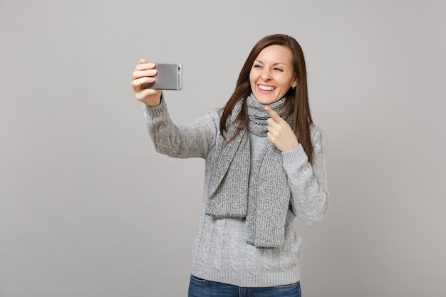 Smiling girl in gray sweater scarf pointing index finger doing selfie shot on mobile phone making video call isolated on grey background. healthy fashion lifestyle people emotions cold season concept.