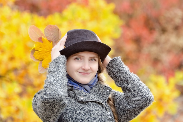 Smiling girl in a hat in autumn park. bright foliage on the background. portrait