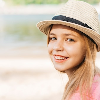 Smiling girl in hat at shore
