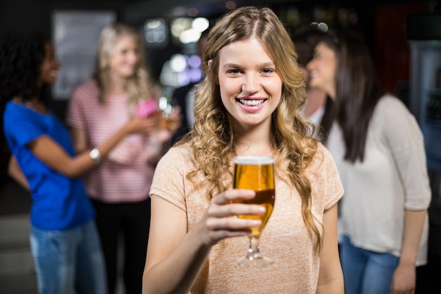Smiling girl having a beer with her friends