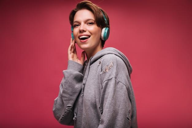 Ragazza sorridente in cuffie esamina la macchina fotografica su sfondo rosa. bella donna in felpa con cappuccio grigia sorride e ascolta musica su isolato