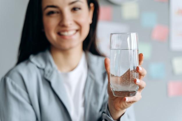 Улыбающаяся девочка держит стакан воды