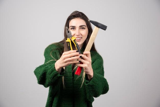 ハンマーとペンチを手に持って笑顔の女の子。