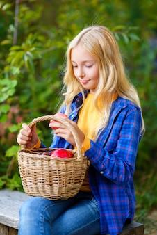 Улыбающаяся девочка держит корзину на открытом воздухе