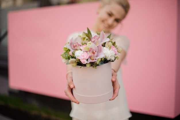 Smiling girl holding bouquet in pink hat box