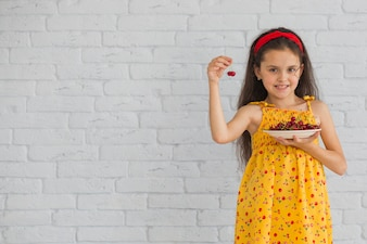 Smiling girl holding cherries in plate standing against brick wall