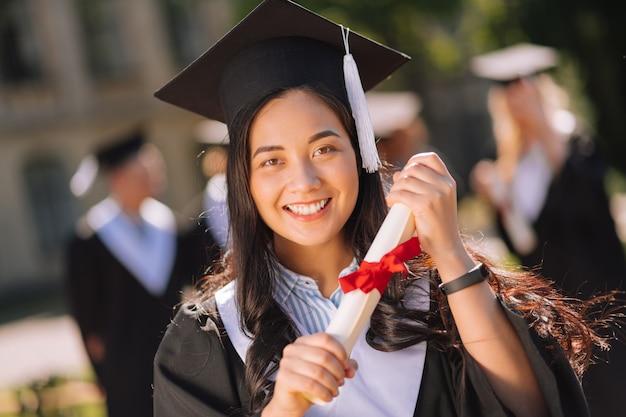 修士号を誇りに思って両手で卒業証書を持っている笑顔の女の子