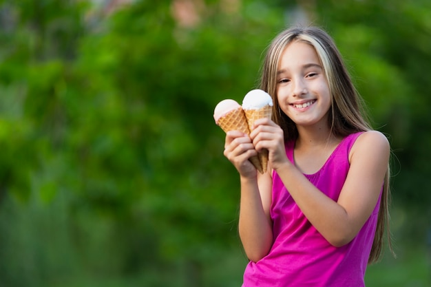 Smiling girl holding ice cream cones