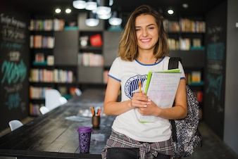 Smiling girl holding notebooks leaning on table