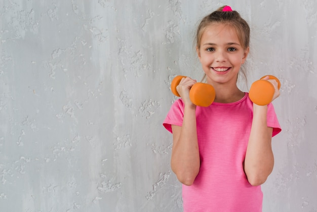 Smiling girl holding orange dumbbell in front of concrete wall