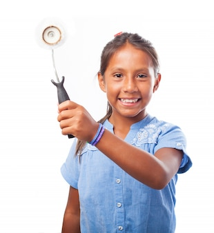 Smiling girl holding a paint roller aside