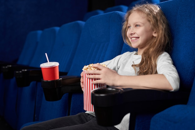 Smiling girl holding popcorn bucket, sitting in cinema.