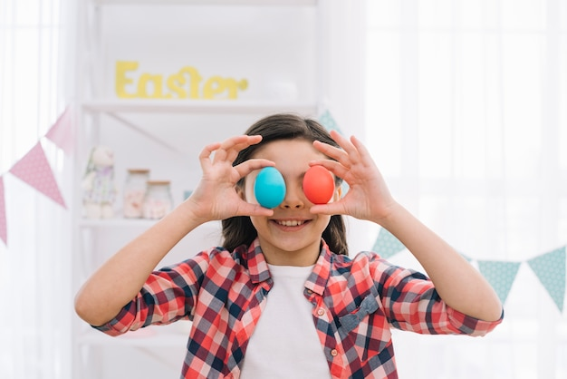 Smiling girl holding red and blue easter eggs over her eyes at home