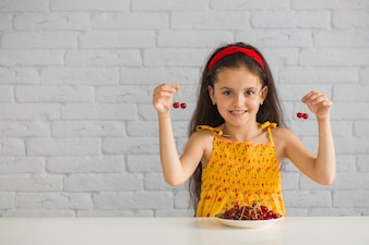 Smiling girl holding red cherries in her hand