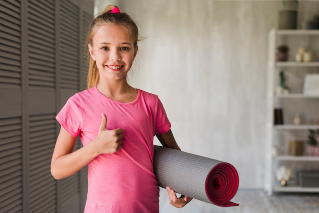 Smiling girl holding rolled up exercise mat showing thumbs up