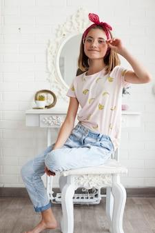 眼鏡を持って、白い木製のテーブルの上に座っている間カメラを見て微笑んでいる女の子