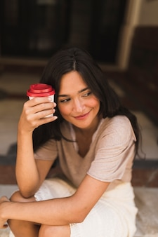 Smiling girl holding takeaway coffee cup