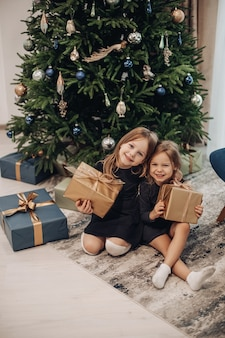 Smiling girl holding their christmas gifts in brown wrapping gifts