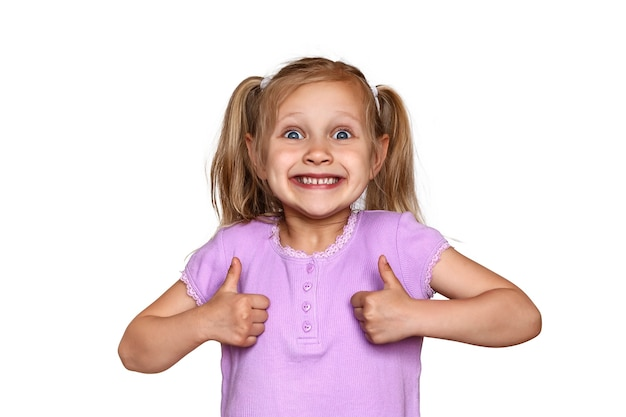 Smiling girl holding thumbs up child on a white background shows she is all right