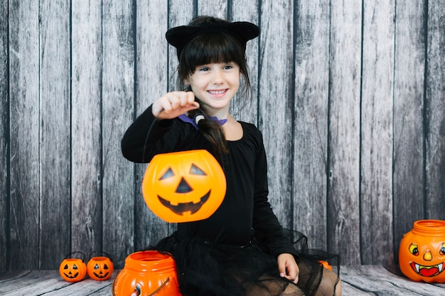 Smiling girl holding trick or treat basket Free Photo