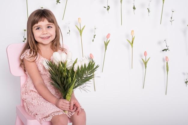 Улыбающаяся девушка держит средний тюльпаны выстрел