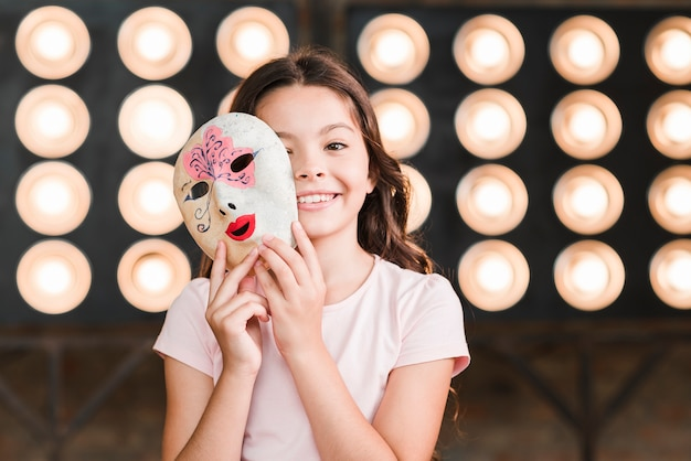 Smiling girl holding venetian mask in her hands standing in front of stage light