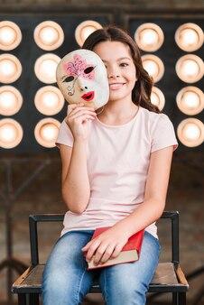 彼女の手の中にベネチアンマスクを持っている笑顔の女の子