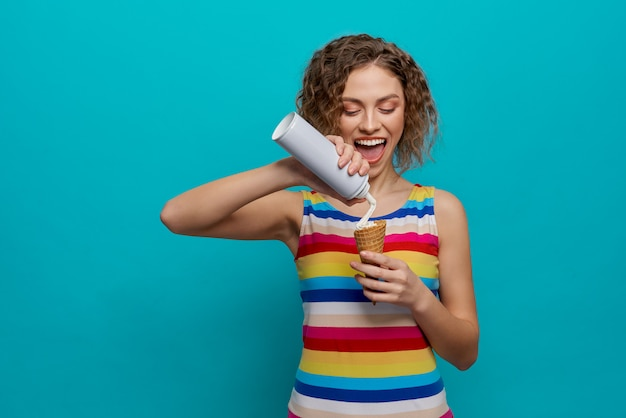 Smiling girl holding wafer cone and whipped cream.