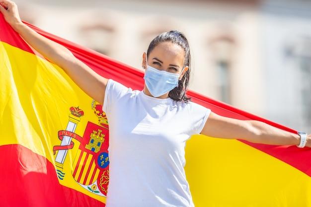 Улыбающаяся девушка в маске держит за спиной испанский флаг.