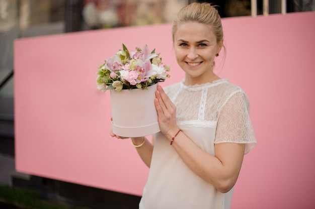 Smiling girl holds bouquet in pink hat box