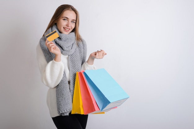 Smiling girl holds a credit card and paper bags in her hand. isolated on gray background.