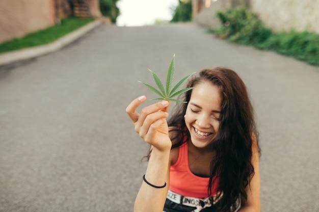 笑顔の女の子は、年に麻の葉を手に持って微笑む