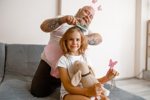 Улыбающаяся девочка держит игрушечную собаку и волшебную палку, пока папа расчесывает ей волосы в комнате
