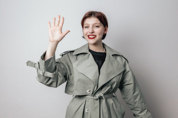 ファッショナブルな緑のコートを着た笑顔の女の子は彼女の手のひらを示しています