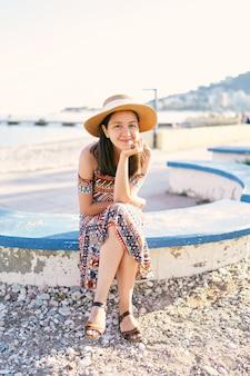 모자와 드레스를 입은 웃는 소녀는 자갈 해변의 벤치에 앉아 있다