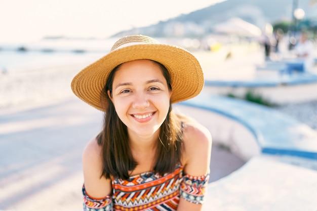 모자와 드레스에 웃는 소녀는 벤치 초상화에 앉아