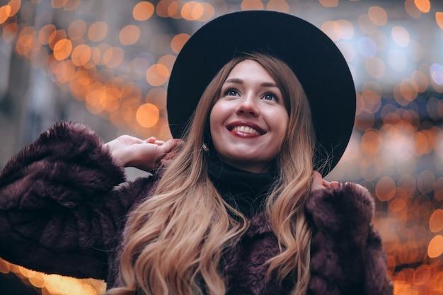 通りを歩いている帽子の笑顔の女の子