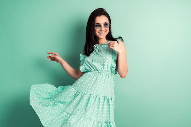 민트 벽에 가벼운 봄 드레스에 웃는 소녀