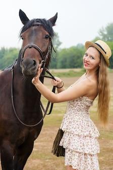 밀짚 모자와 여름 드레스에 웃는 소녀는 말과 함께 촬영